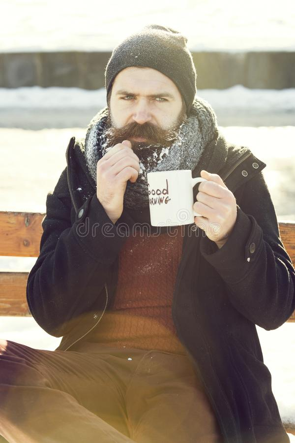 Frown man, bearded hipster with beard and moustache covered with white frost drinks from cup with good morning text. Sitting on wooden bench on snowy winter day stock photos
