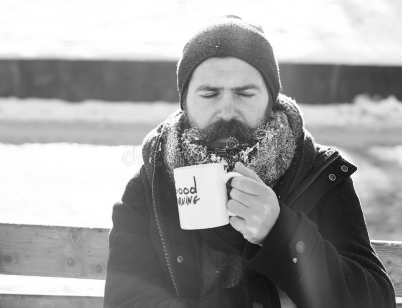 Frown man, bearded hipster with beard and moustache covered with white frost drinks from cup with good morning text. Sitting on wooden bench on snowy winter day stock photo