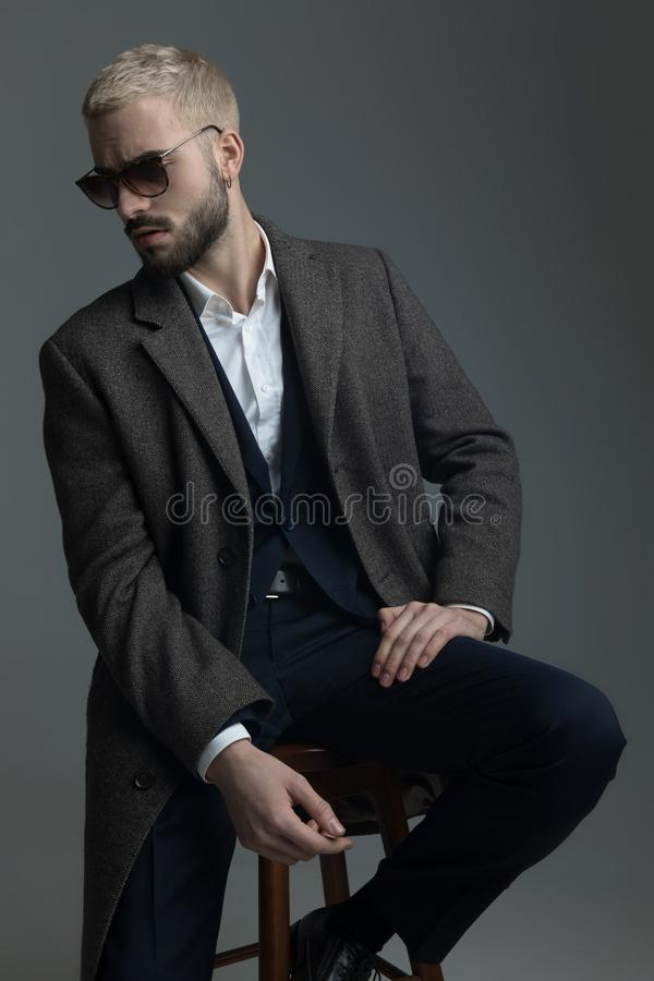 Frown man with sunglasses hold his hand on knee stock photos