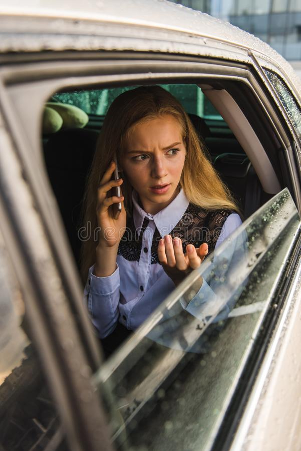 Portrait of girl talk by cellphone, sit in car. Frown young woman gesture during phone conversation. Portrait of girl talk by cellphone, sit in car at rainy day stock photo