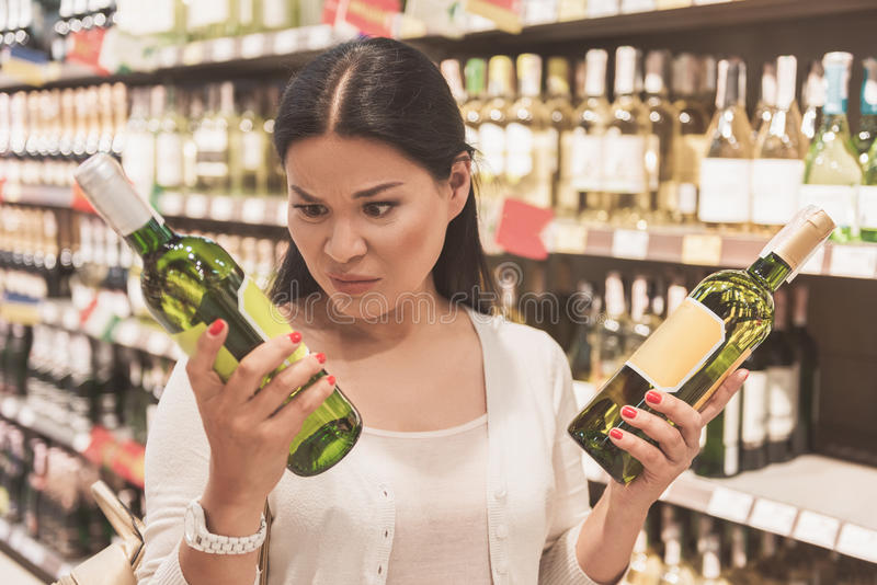Frowned adult lady keeping beverage. Confused woman is holding bottle of white wine and looking at one with discontentment. She standing in supermarket. Portrait royalty free stock photos