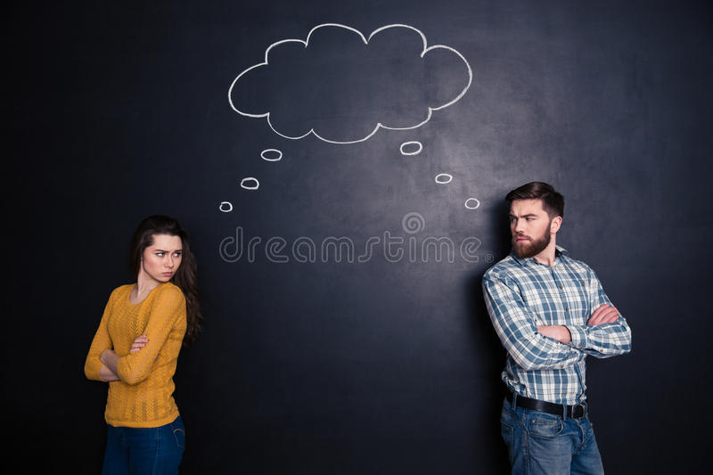 Frowning angry couple thinking identically over background of chalkboard. Frowning angry young couple standing with hands folded and thinking identically over stock photography