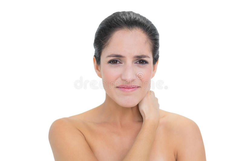 Frowning Bare Brunette Touching Her Neck Royalty Free Stock Photography