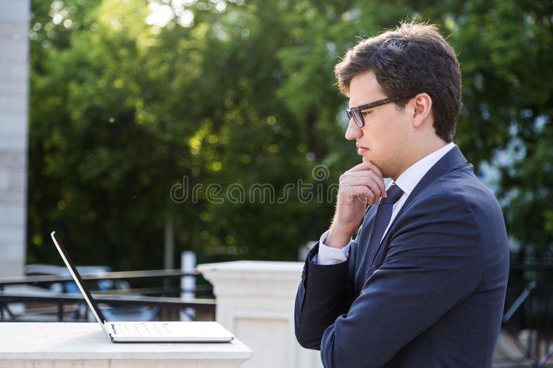 Frowning businessman looking at laptop stock photography
