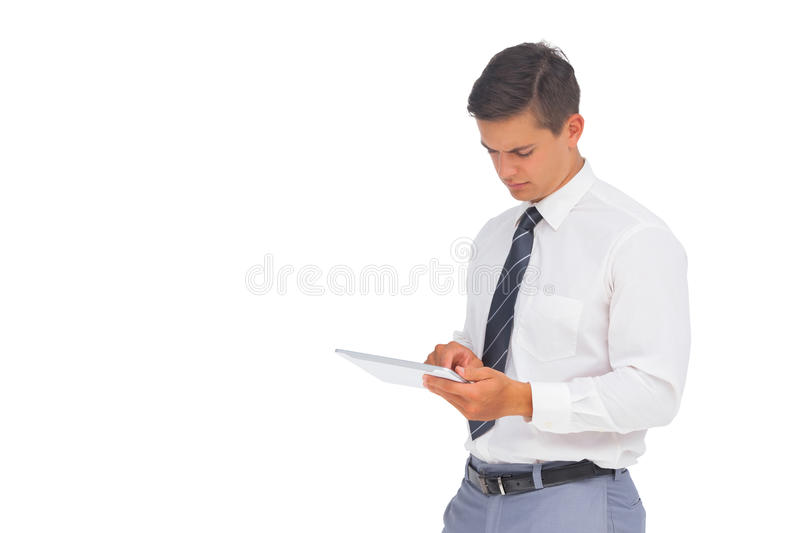 Frowning businessman using tablet