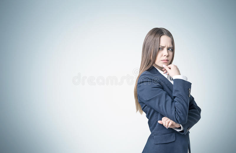 Frowning businesswoman near a gray wall royalty free stock photo
