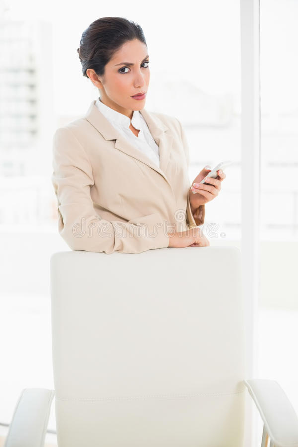 Frowning businesswoman standing behind her chair holding her phone glaring at camera royalty free stock image