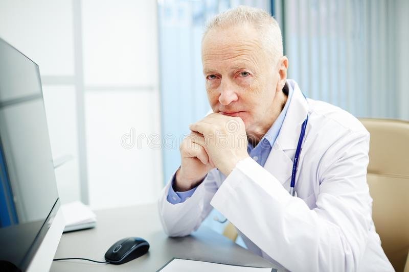 Frowning general practitioner in own office royalty free stock photography