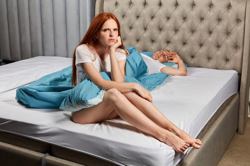 Frowning ginger girl sitting on the bed, expressing negative feeling. Is being offended by her husband. close up photo stock photos