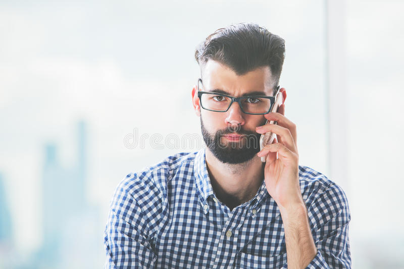 Frowning man on phone. Frowning young man on phone. Close up portrait royalty free stock images