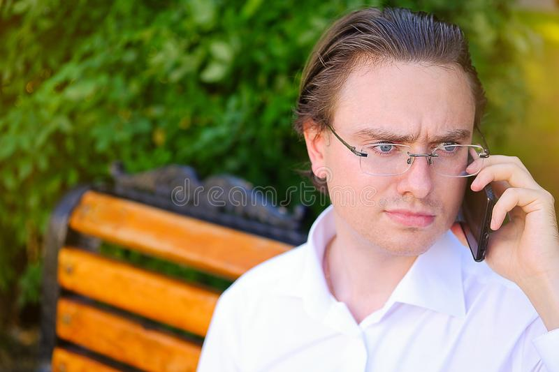 Frowning and serious man-Manager, freelancer, businessman in glasses working outdoors. Communicates, talking on a mobile phone royalty free stock image