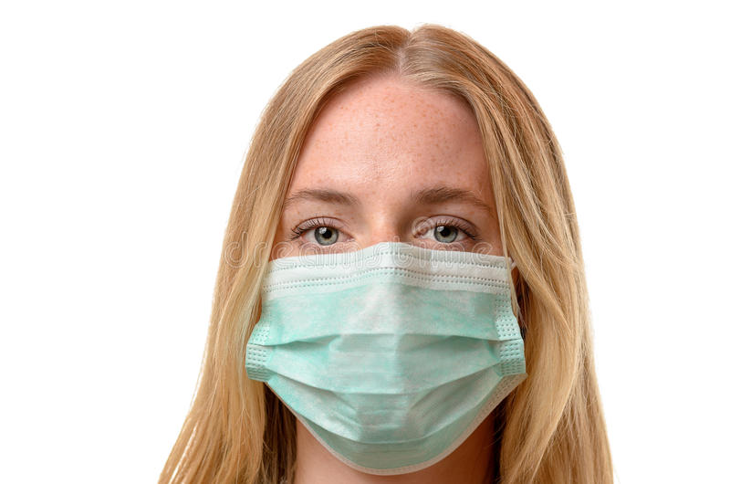 Frowning young woman wearing a face mask. Frowning young blond woman wearing a face mask as protection against airborne diseases and pollution, close up head stock photos