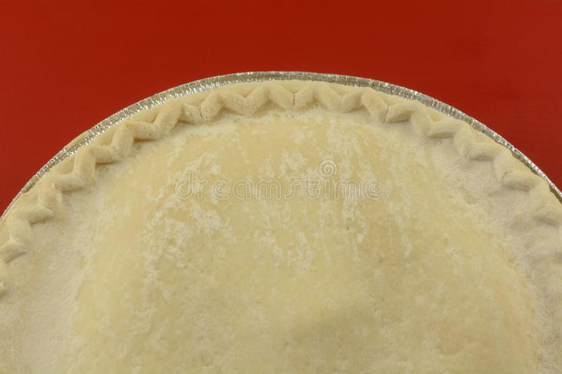 Frozen apple pie on red. Close up of uncooked frozen apple pie on red background royalty free stock photo