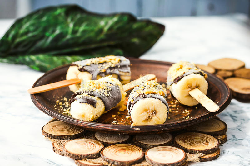 Frozen bananas with chocolate and nuts, raw summer dessert. Frozen bananas with chocolate and nuts, raw summer healthy dessert, selective focus stock photo