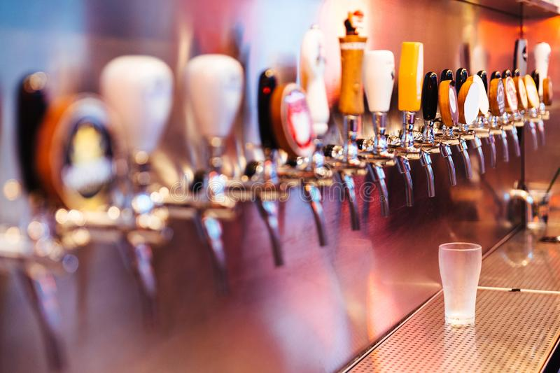 Frozen beer glass with beer taps with nobody. Selective focus. Alcohol concept. Vintage style. Beer craft. Bar table. Steel taps. Shiny taps royalty free stock photos