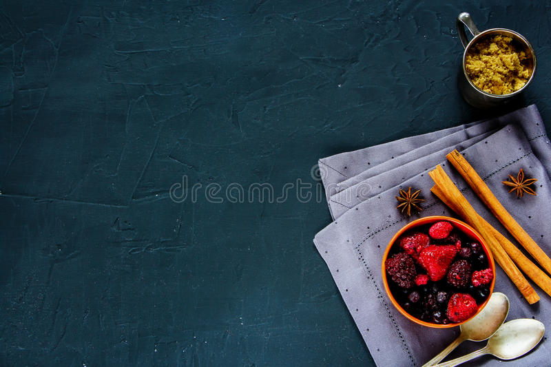 Frozen berries with brown sugar. Frozen berries mix with brown sugar and spices over rustic background, place for text, top view stock photo