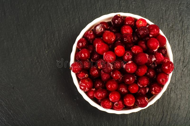 Frozen berries of cranberries in white bowl on black stone stock images