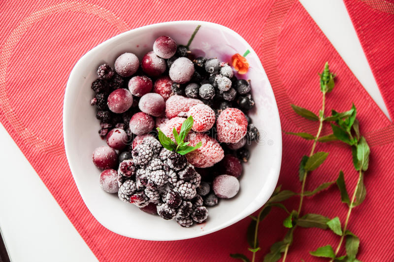 Frozen berries on plate with a bunch of mint stock photography