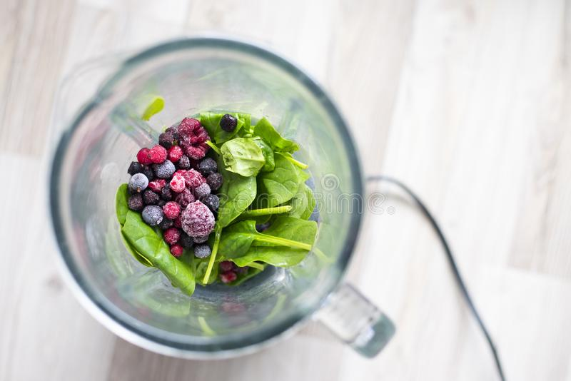 Frozen berries and spinach leaf ready for smoothie blending stock photography