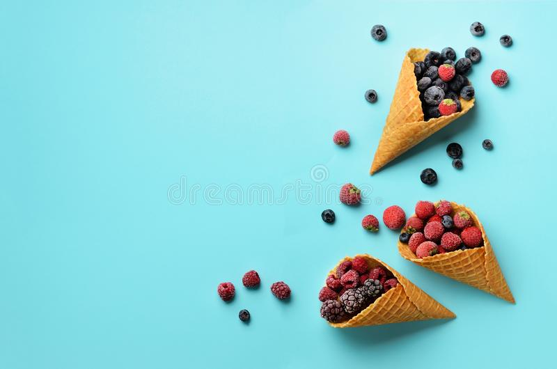 Frozen berries - strawberry, blueberry, blackberry, raspberry in waffle cones on blue background. Top view. Banner royalty free stock photography
