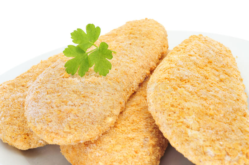 Frozen breaded fish. Closeup of a plate with some pieces of frozen breaded fish on a white background ready to be cooked royalty free stock images