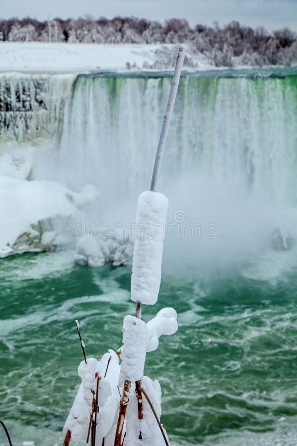 Frozen rush in front of waterfall. Frozen bull rush covered in snow in midwinter in front of Niagara falls in Canada royalty free stock image