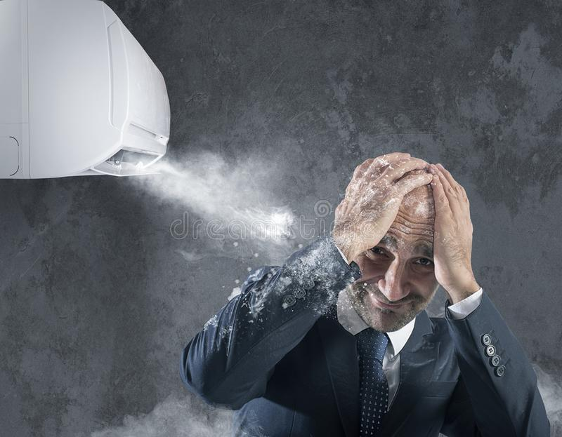 Businessman tries to protect from himself icy air conditioner royalty free stock images