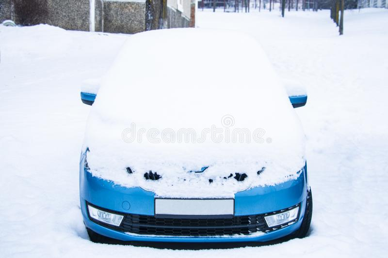 Frozen car covered snow at winter day, view front window windshield and hood on snowy background stock photo