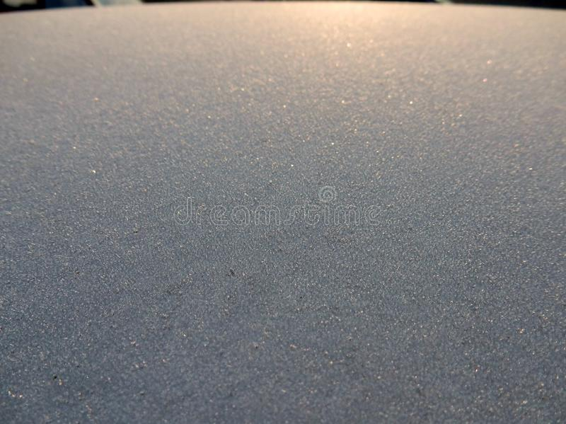 Frozen car at dawn. First reflections of the morning sun on the icy roof of a car royalty free stock image