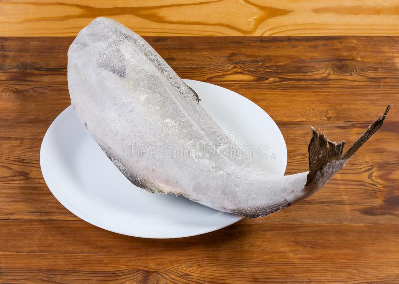 Frozen carcass of saithe without head on the dish. Frozen carcass of saithe, also known as coalfish without head on dish on the rustic table stock image