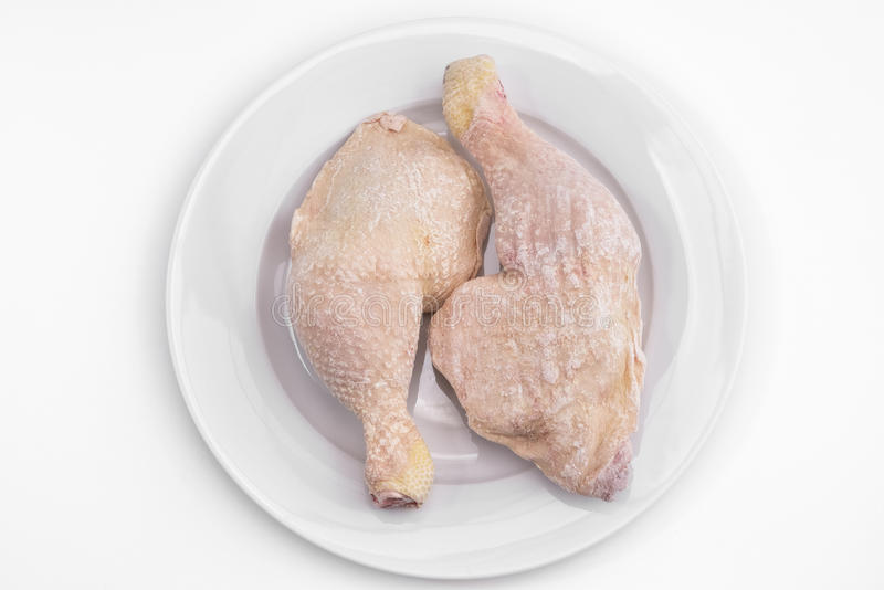 Frozen chicken legs on a plate royalty free stock photo