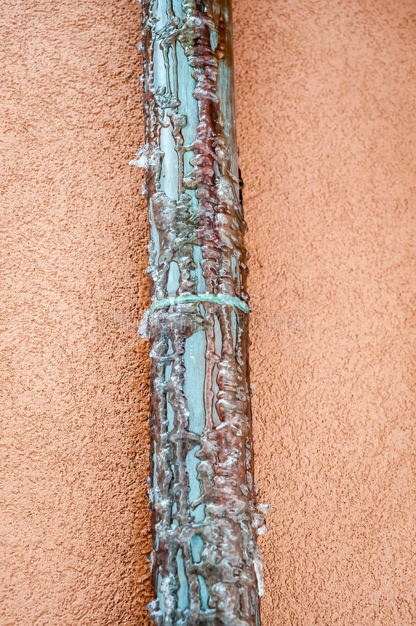 Frozen copper pipe. Water drain from house roof royalty free stock photo