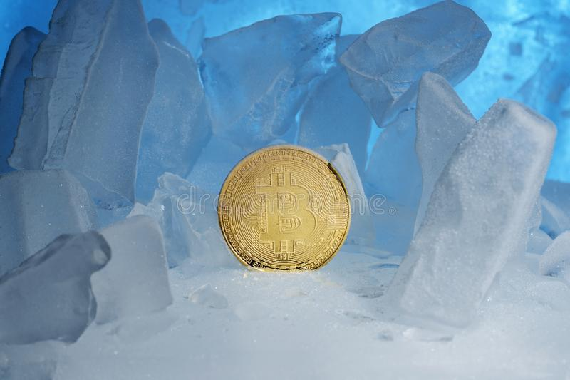 Frozen crypto currency bitcoin face obverse stands surrounded by blue ice in beautiful light. Frozen crypto currency bitcoin face obverse stands surrounded by royalty free stock images