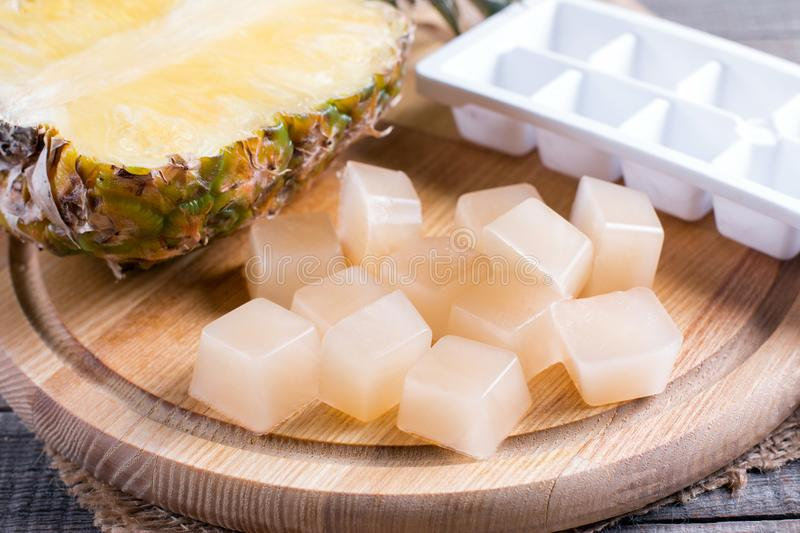 Frozen cubes of pineapple juice on a wooden table. Freezing royalty free stock image
