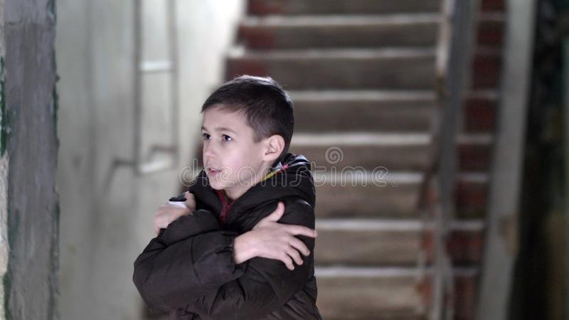 Frozen curious wary boy walks to a dilapidated old house. Have fun royalty free stock photography