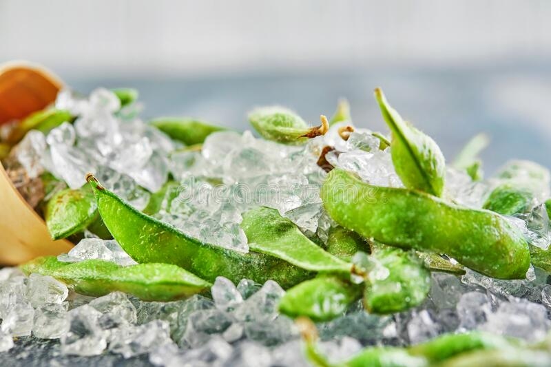 Frozen Edamame or soybeans in the mix with crushed ice on a blue background stock image