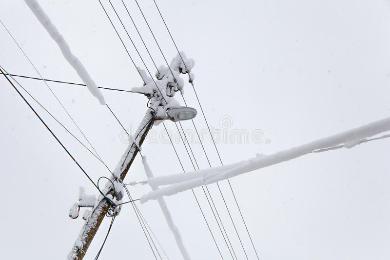 Frozen Electric Power Pole. Falling snow on a frozen electric power pole in a cold winter day stock image