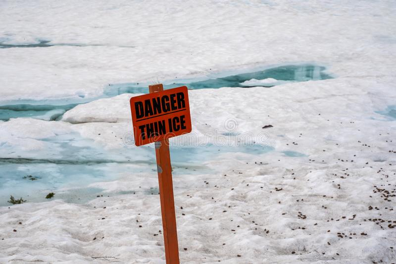Frozen Emerald Lake in Lassen National Park with blue ice and snow, in California. Sign warns of Danger, Thin Ice.  royalty free stock photos