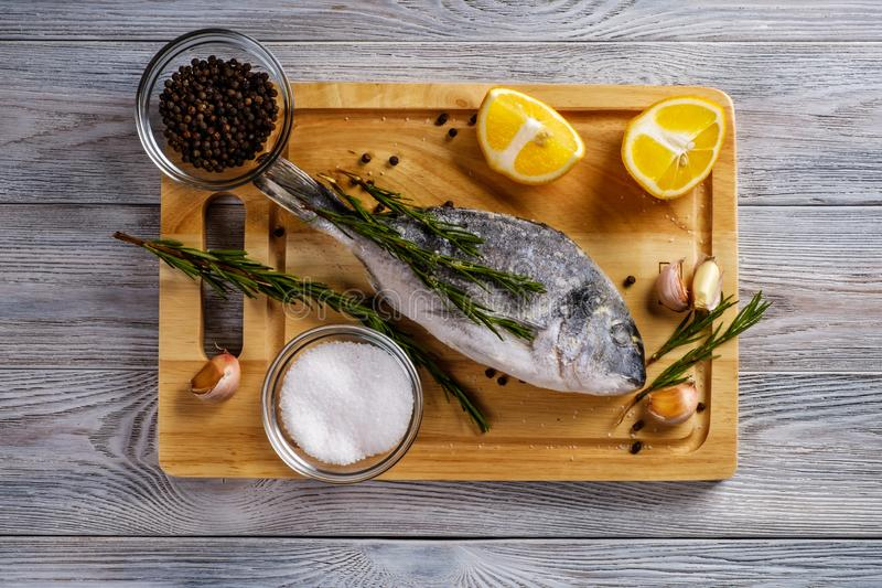 Frozen fish dorado with lemon and spices on wooden board. Healthy food. Frozen fish dorado on wooden board royalty free stock photo