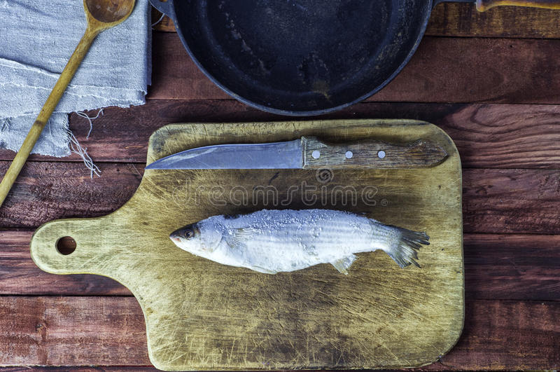 Frozen fish smelt on the kitchen board royalty free stock photography