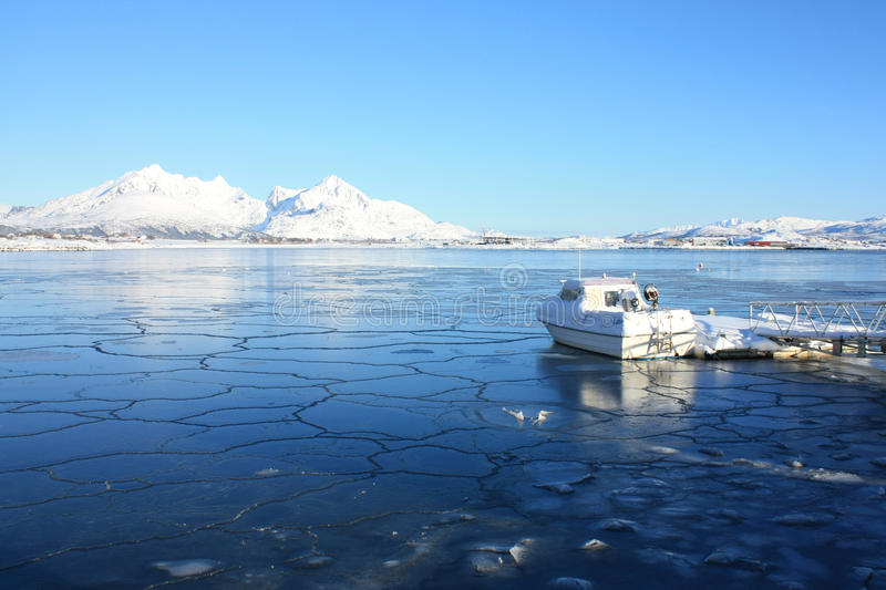 Frozen fjord with boat. Boat on an icy bay of Busknes fjord, lofoten islands royalty free stock photography