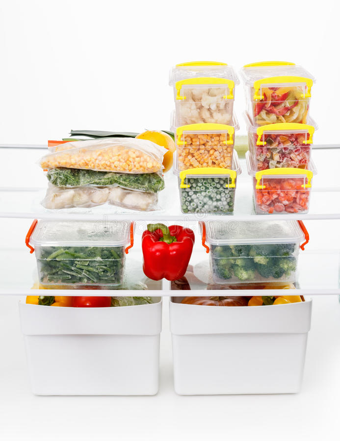Frozen food in the refrigerator. Vegetables on the freezer shelves. Stocks of meal for the winter stock images