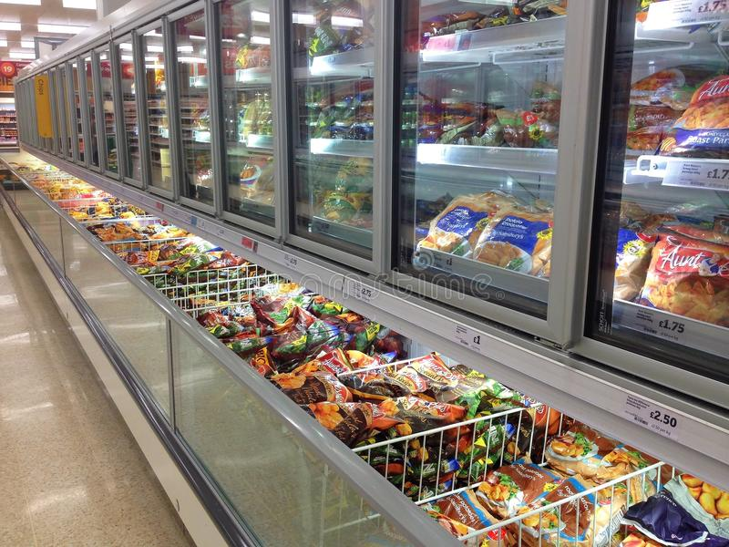 Frozen food in supermarket freezers. Frozen goods in lines of freezers at a superstore or supermarket. This is in the Sainsbury supermarket, Bedford, United royalty free stock photo