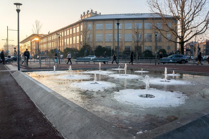 Frozen fountains on the background of walking people and buildings on the street in the winter, in a residential area. Milan, Nuovo Portello / Italy - January 22 royalty free stock photos