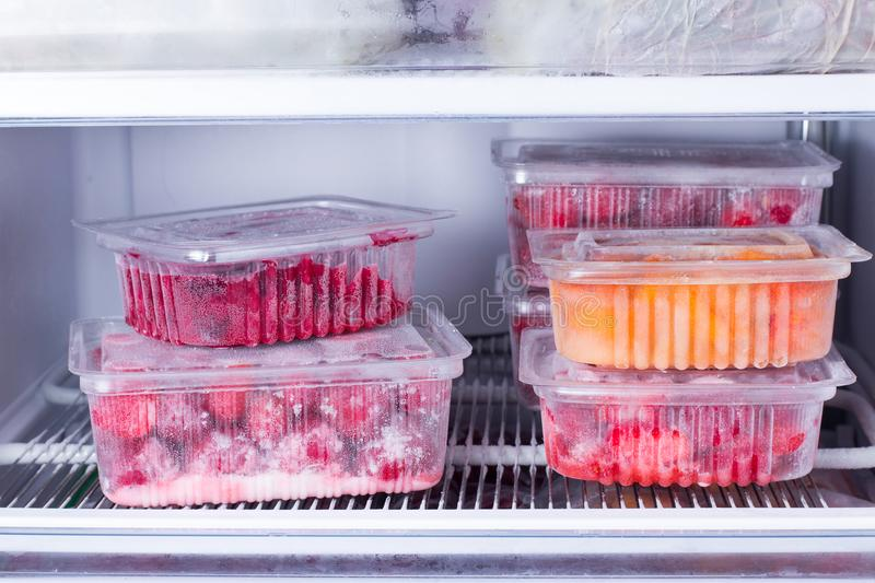 Frozen fruits and berries in a container in the freezer stock images