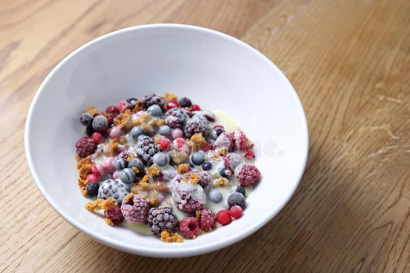 Frozen fruits with granola and yogurt, healthy fruit breakfast royalty free stock photo