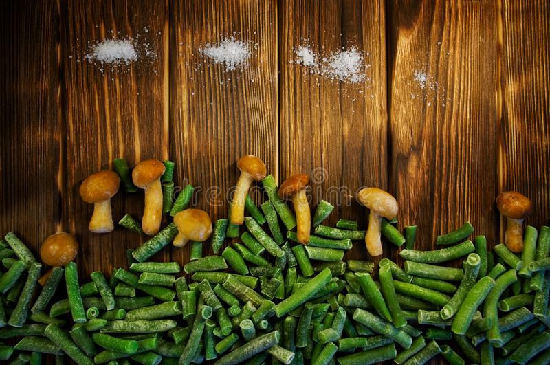 Frozen fungus mushrooms, green beans and salt on a wooden background. Imitation of a forest clearing and clouds stock photo
