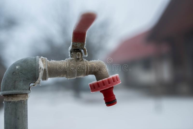 Frozen garden water tap on a cold winter morning, shallow depth of field. Space for text stock image