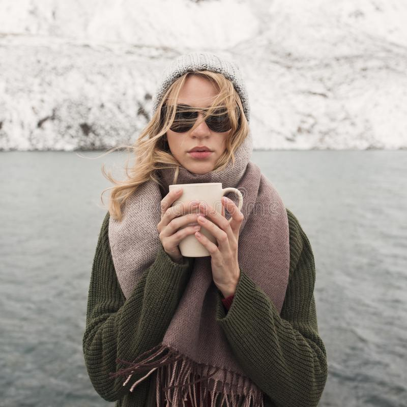 Frozen girl holds a cup of hot coffee. Mountain lake royalty free stock photo