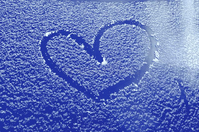 Frozen glass of a car on a winter day, drawing heart stock photos